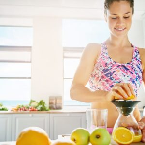 Smiling sporty lady making orange juice