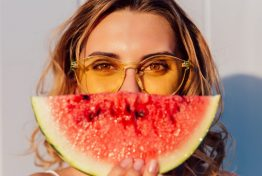 Charming lovely woman in yellow sunglasses hiding a half of her face with piece of watermelon, joking, standing against the wall, outdoors.
